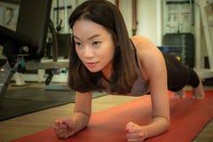 Μια ασιατική όμορφη γυναίκα κάνει μια σανίδα στοκ φωτογραφία