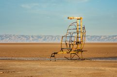 Μια αστεία μεταλλική καρέκλα στη μεγάλη αλατισμένη λίμνη Chott EL Jerid στοκ εικόνα