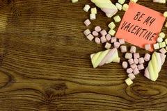 Μια αυτοκόλλητη ετικέττα με το κείμενο: Να είστε ο βαλεντίνος μου που διακοσμείται με marshmallow τα γλυκά Έννοια αγάπης στο ξύλι Στοκ φωτογραφία με δικαίωμα ελεύθερης χρήσης