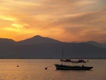 Μια βάρκα που επιπλέει στο Αιγαίο πέλαγος κάτω από τον όμορφο χρυσό ουρανό μετά από το ηλιοβασίλεμα στοκ εικόνες