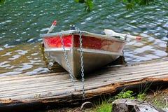 Μια βάρκα σειρών αργιλίου που αλυσοδένεται στην ακτή από μια αποβάθρα Στοκ φωτογραφία με δικαίωμα ελεύθερης χρήσης