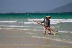 Μια βιετναμέζικη γυναίκα συλλέγει τα κοχύλια θάλασσας στην ακτή σε Nha Trang, Βιετνάμ Στοκ φωτογραφία με δικαίωμα ελεύθερης χρήσης