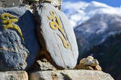 Μια βουδιστική πέτρα mani ή πέτρα προσευχής στο κύκλωμα Annapurna με από την εστίαση καλυμμένα χιόνι Ιμαλάια πίσω Νεπάλ Στοκ Εικόνες
