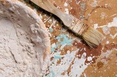 Μια βούρτσα έπειτα ένα κύπελλο με ξηρό putty σε μια ινόπλακα Στοκ Φωτογραφίες