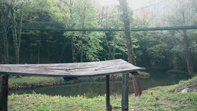 Μια γέφυρα περπατήματος πέρα από τον ποταμό στο βουνό Το παλαιό ξύλινο γραφείο στο μέτωπο απόθεμα βίντεο