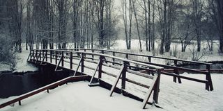 Μια γέφυρα που καλύπτεται ξύλινη με το χειμώνα χιονιού στη Ρωσία Στοκ εικόνες με δικαίωμα ελεύθερης χρήσης
