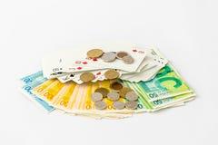 Μια γέφυρα των καρτών παιχνιδιού με τα νομίσματα βρίσκεται σε έναν σωρό των τραπεζογραμματίων και των νομισμάτων των νέων ισραηλι Στοκ Φωτογραφίες