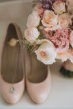 Μια γαμήλια ανθοδέσμη των ρόδινων τριαντάφυλλων δίπλα στα παπούτσια γυναικών ` s και ένα κρεμαστό κόσμημα με μια μπλε πέτρα Στοκ φωτογραφία με δικαίωμα ελεύθερης χρήσης