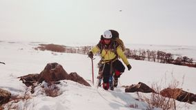 Μια γενναία ομάδα ορειβατών αναρριχείται να υπερνικήσει τον αυστηρό χειμερινό καιρό και το χιόνι επάνω ένας μεγάλος και απότομος  απόθεμα βίντεο