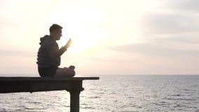 Μια γιόγκα πρακτικών ατόμων με μια άποψη ηλιοβασιλέματος της θάλασσας απόθεμα βίντεο