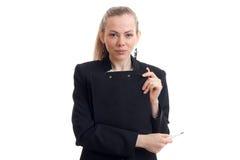 Μια γοητευτική νέα επιχειρησιακή γυναίκα φαίνεται ευθεία και κρατώντας μια μαύρη κινηματογράφηση σε πρώτο πλάνο ταμπλετών Στοκ Εικόνες