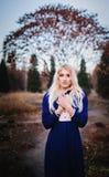 Μια γυναίκα έντυσε παραμονές στις μπλε εκλεκτής ποιότητας φορεμάτων στο πάρκο φθινοπώρου Στοκ Εικόνα