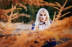Μια γυναίκα έντυσε παραμονές στις μπλε εκλεκτής ποιότητας φορεμάτων στο πάρκο φθινοπώρου Στοκ Εικόνες