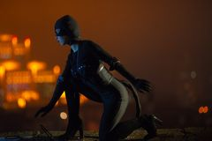 Μια γυναίκα έντυσε ως γάτα σε ένα μαύρο κοστούμι, γάντια και μια μάσκα, κάθεται στα πλαίσια των φω'των νύχτας και του ουρανού στοκ εικόνες με δικαίωμα ελεύθερης χρήσης