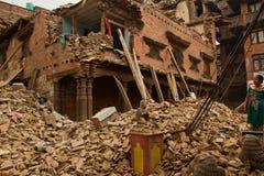 Μια γυναίκα έξω από τώρα το σεισμό της κατέστρεψε το σπίτι σε Bhaktapur, ΝΕ στοκ εικόνες