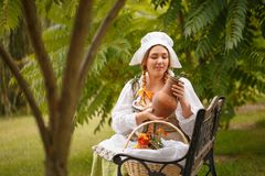 Μια γυναίκα αγροτών που εξετάζει μια συνεδρίαση σταμνών σε ένα μικρό καπάκι Στοκ Εικόνες