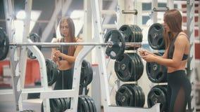 Μια γυναίκα αθλητών που εκπαιδεύει στη γυμναστική - που βάζει ένα βάρος στον αλτήρα απόθεμα βίντεο