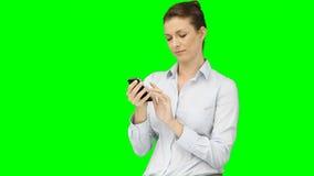 Μια γυναίκα δακτυλογραφεί στο smartphone της και χαμογελά απόθεμα βίντεο