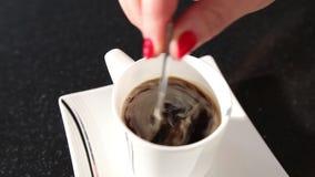 Μια γυναίκα ανακατώνει έναν καφέ με ένα κουτάλι, ένα κορίτσι ανακατώνει τη ζάχαρη σε ένα κουτάλι καφέ, κινηματογράφηση σε πρώτο π απόθεμα βίντεο