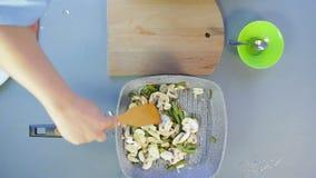 Μια γυναίκα αναμιγνύει τα φασόλια και το κρεμμύδι με τη σάλτσα σόγιας σε ένα τηγάνι με ξύλινο spatula r απόθεμα βίντεο
