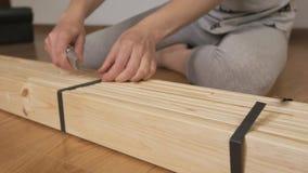 Μια γυναίκα ανοίγει ένα ξύλινο ράφι, που αγοράζεται στο κατάστημα, κόβει τη συσκευάζοντας ταινία με ένα μαχαίρι Χέρια με μια κινη φιλμ μικρού μήκους