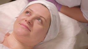 Μια γυναίκα ανοίγει τα μάτια της μετά από τη διαδικασία το δέρμα στο σαλόνι ομορφιάς Υγεία και ομορφιά Κινηματογράφηση σε πρώτο π φιλμ μικρού μήκους