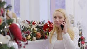 Μια γυναίκα απαιτεί Χριστούγεννα στο κινητό τηλέφωνό της για να ευχηθεί αγαπημένο τη Χαρούμενα Χριστούγεννα όταν στέκεται μπροστά φιλμ μικρού μήκους