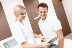 Μια γυναίκα από ένα σαλόνι ομορφιάς παρουσιάζει πληροφορίες ανδρών για τις διαδικασίες στην γκρίζα ταμπλέτα του Στοκ φωτογραφία με δικαίωμα ελεύθερης χρήσης