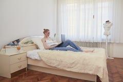 Μια γυναίκα, αργός πολιτισμός, που χρησιμοποιεί το lap-top, που βάζει στη χαλάρωση κρεβατιών συνηθισμένο μεγάλο εσωτερικό δωματίω στοκ εικόνα με δικαίωμα ελεύθερης χρήσης