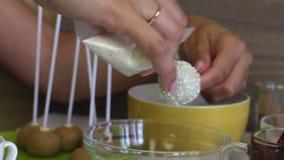 Μια γυναίκα βάζει μια άσπρη τήξη στο κέικ σκάει, καλυμμένος με την άσπρη σοκολάτα Για ακόμη και τη διανομή της σάλτσας στη σφαίρα απόθεμα βίντεο