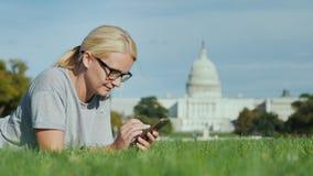 Μια γυναίκα βρίσκεται σε έναν χορτοτάπητα στα πλαίσια του Capitol στην Ουάσιγκτον, συνεχές ρεύμα Χρησιμοποιεί ένα smartphone Τουρ απόθεμα βίντεο