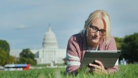 Μια γυναίκα βρίσκεται σε έναν χορτοτάπητα στα πλαίσια του Capitol στην Ουάσιγκτον, συνεχές ρεύμα Χρησιμοποιεί μια ταμπλέτα Τουρισ φιλμ μικρού μήκους