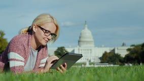 Μια γυναίκα βρίσκεται σε έναν χορτοτάπητα στα πλαίσια του Capitol στην Ουάσιγκτον, συνεχές ρεύμα Χρησιμοποιεί μια ταμπλέτα Τουρισ απόθεμα βίντεο