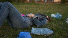 Μια γυναίκα βρίσκεται στη χλόη στη μέση των πλαστικών απορριμμάτων Πλαστική, πλαστική ρύπανση στάσεων του πλανήτη απόθεμα βίντεο