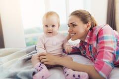 Μια γυναίκα βρίσκεται στο κρεβάτι δίπλα στο μωρό Θα βάλει το μωρό στο κρεβάτι Στοκ Εικόνα
