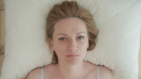 Μια γυναίκα βρίσκεται στο κρεβάτι και ανοίγει αισθητά τα μάτια της, εξετάζει τη κάμερα Κινηματογράφηση σε πρώτο πλάνο επάνω από τ φιλμ μικρού μήκους