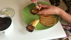 Μια γυναίκα διακοσμεί με μια πολύχρωμη σάλτσα έναν κώνο βαφλών που βυθίζεται στη λειωμένη σοκολάτα απόθεμα βίντεο