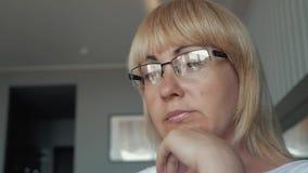 Μια γυναίκα είναι ένας επιχειρηματίας που εξετάζει μια οθόνη υπολογιστή Ένα κορίτσι ντύνει τα γυαλιά στενό σε επάνω ματιών Να εργ απόθεμα βίντεο