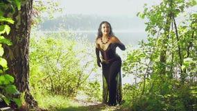 Μια γυναίκα είναι μάγισσα στα μαύρα ενδύματα στην ακτή μιας λίμνης αποκριές Ύφος Gothick απόθεμα βίντεο