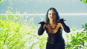 Μια γυναίκα είναι μάγισσα στα μαύρα ενδύματα στη λίμνη με τις συγκινήσεις του θυμού στο πρόσωπό της αποκριές Ύφος Gothick φιλμ μικρού μήκους