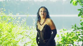 Μια γυναίκα είναι μάγισσα στα μαύρα ενδύματα στη λίμνη με τις συγκινήσεις στο πρόσωπό της αποκριές Styl Gothick απόθεμα βίντεο