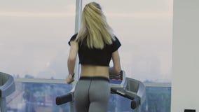 Μια γυναίκα εκπαιδεύει treadmill σε μια λέσχη ικανότητας απόθεμα βίντεο