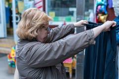 Μια γυναίκα εξετάζει προσεκτικά τα ενδύματα πρίν αγοράζει στοκ φωτογραφία