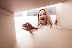 Μια γυναίκα εξετάζει το κενό κιβώτιο από το εσωτερικό Φωτογραφία κινηματογραφήσεων σε πρώτο πλάνο μιας γυναίκας που κοιτάζει αδιά Στοκ Εικόνα