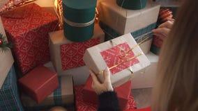 Μια γυναίκα εξετάζει δώρα το χριστουγεννιάτικο δέντρο φιλμ μικρού μήκους