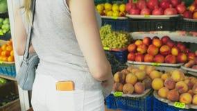 Μια γυναίκα επιλέγει τα λαχανικά στην αγορά 4K αργός πυροβολισμός απόθεμα βίντεο