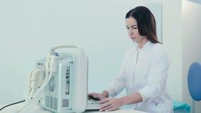 Μια γυναίκα εργάζεται με μια συσκευή υπερήχου στην κλινική απόθεμα βίντεο