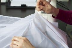 Μια γυναίκα εργάζεται σε μια ράβοντας μηχανή Ράβει τις κουρτίνες στο παράθυρο Στοκ φωτογραφία με δικαίωμα ελεύθερης χρήσης
