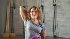 Μια γυναίκα 35-40 ετών κάνει το πιάσιμο καρπός-κλειδαριών πίσω από την πλάτη φιλμ μικρού μήκους