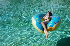 Μια γυναίκα θέτει πέρα από μια σαφή λίμνη aqua στοκ εικόνες